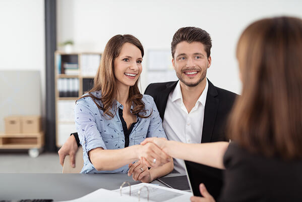 Happy Young Professional Couple Shaking Hands with a Real Estate Agent After Some Business Discussions Inside the Office.-1